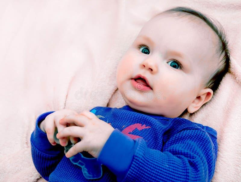 Weinig babymeisje op roze achtergrond in purpere blouse royalty-vrije stock foto's