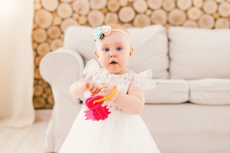 Weinig babymeisje in witte overvloedige kleding die in woonkamer zich binnenshuis op bank en houten muurachtergrond bevinden en a royalty-vrije stock foto