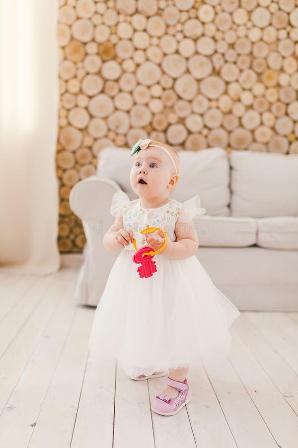 Weinig babymeisje in witte overvloedige kleding die in woonkamer zich binnenshuis op bank en houten muurachtergrond bevinden en a stock afbeeldingen