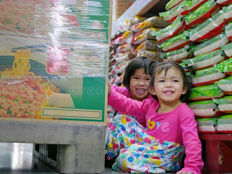 Weinig babymeisjes, zusters die, die/achter grote dozen van onmiddellijke noedels spelen verbergen bij een supermarkt - huid - en royalty-vrije stock foto's