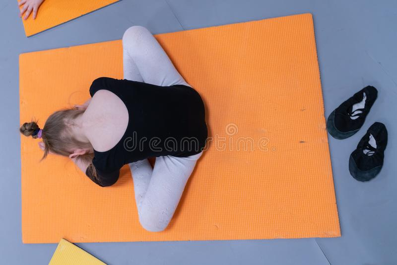 Weinig ballerina die oefeningen en kromming doen, die op de vloer in de balletklasse zitten royalty-vrije stock afbeelding