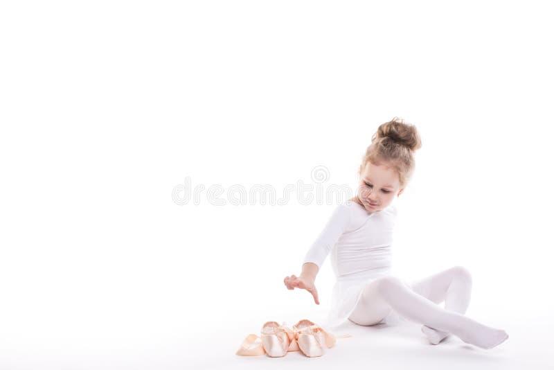 Weinig Ballerina en balletschoenen op een witte achtergrond stock fotografie