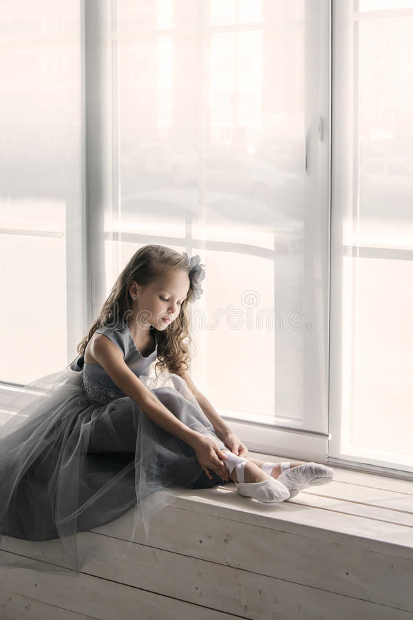 Weinig ballerina in grijze kleding zet op de voorzijde van balletschoenen pointe royalty-vrije stock afbeeldingen