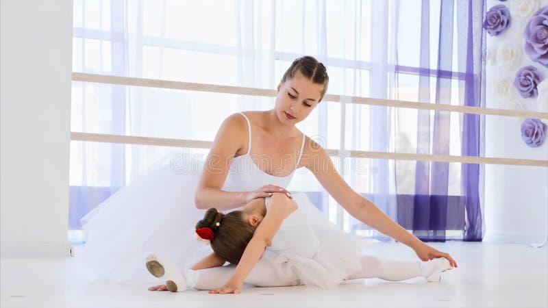 Weinig ballerina in witte tutu rekt zich met balletleraar uit royalty-vrije stock fotografie