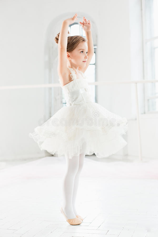 Weinig ballerinameisje in een tutu Aanbiddelijk kind het dansen klassiek ballet in een witte studio stock afbeeldingen
