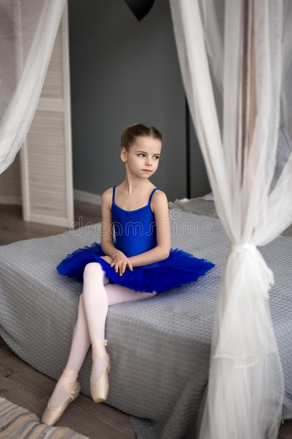 Weinig ballerinazitting op een bed Leuke meisjedromen van het worden een ballerina stock foto's