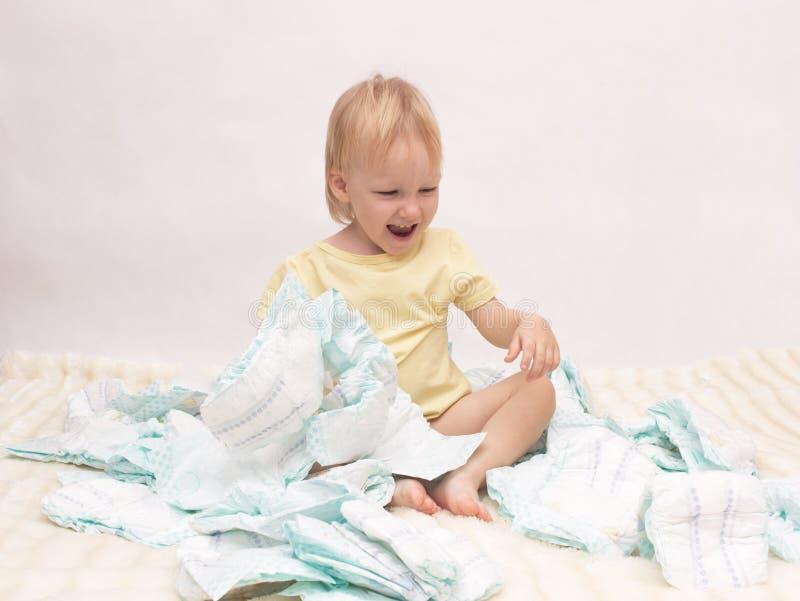Weinig blij meisje die met een stapel van luiers op een witte achtergrond, exemplaarruimte, servet spelen stock foto's