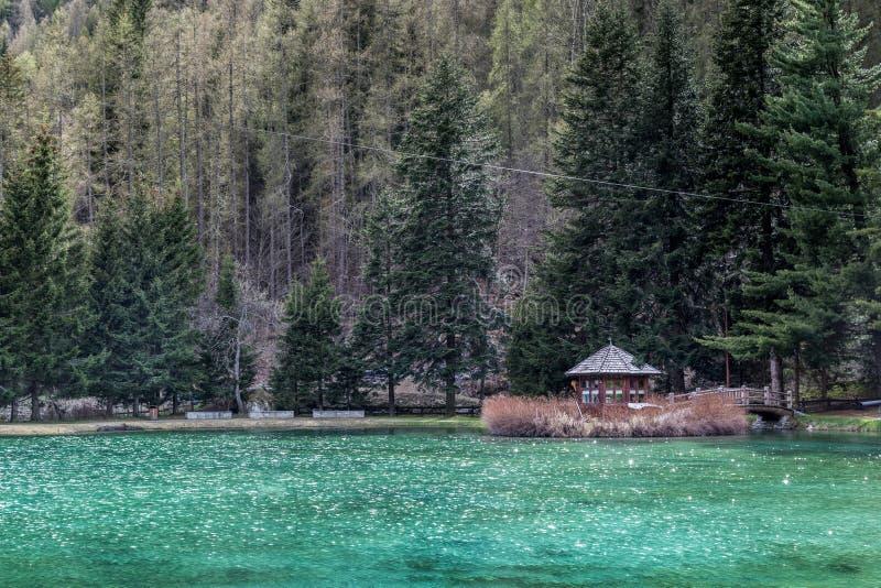 Weinig Blokhuis De bergen en de bomen denken in een koud meer in Gressoney na royalty-vrije stock fotografie