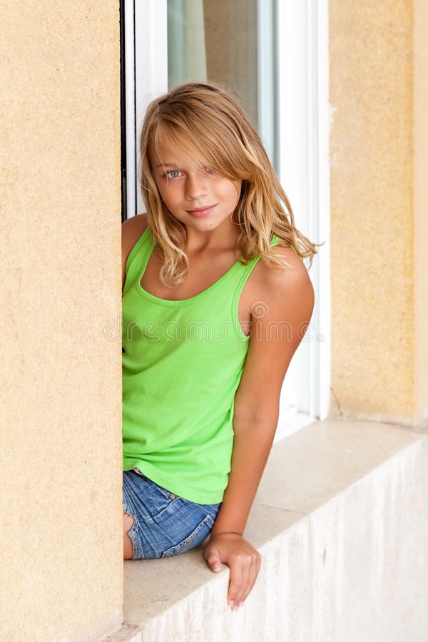 Weinig blond Kaukasisch meisje in het venster royalty-vrije stock foto