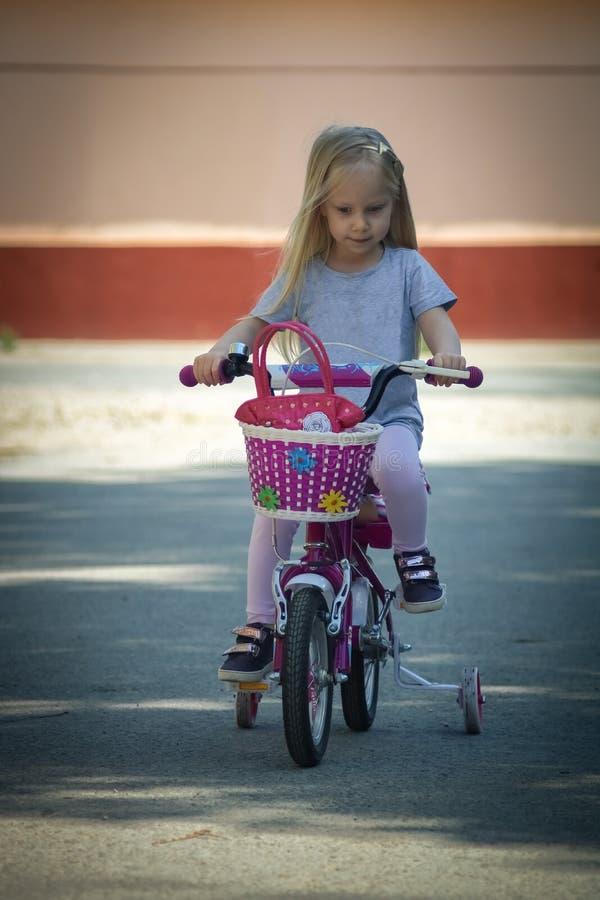 Weinig blond meisje berijdt een fiets op een zonnige dag royalty-vrije stock afbeeldingen