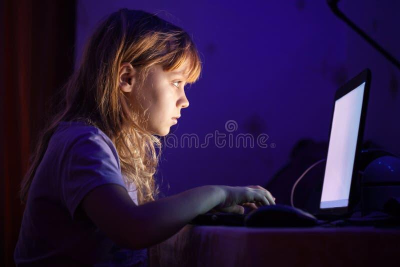 Weinig blond meisje die aan laptop in dark werken royalty-vrije stock foto