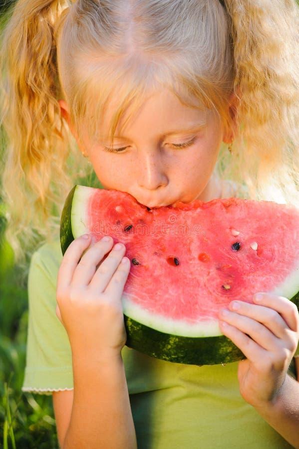 Weinig blond meisje die een stuk van watermeloenportret eten op natur stock afbeelding