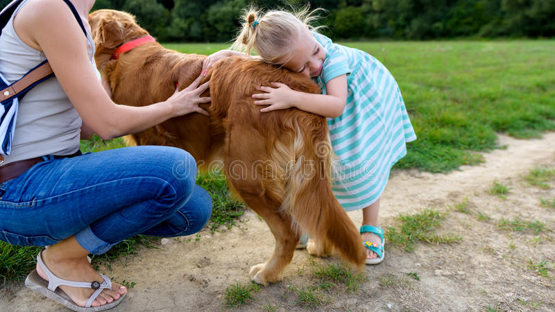 Weinig blond meisje die en haar leuk golden retriever van de huisdierenhond glimlachen koesteren royalty-vrije stock foto