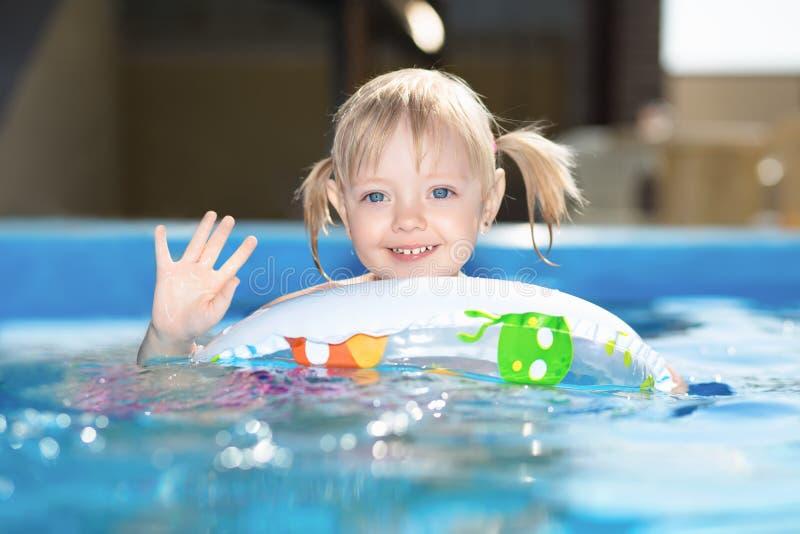 Weinig blond meisje die in waterpool zwemmen stock fotografie