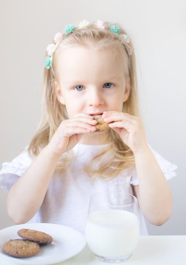 Weinig blond meisje drinkt een glas melk met verschillende emoties royalty-vrije stock afbeelding