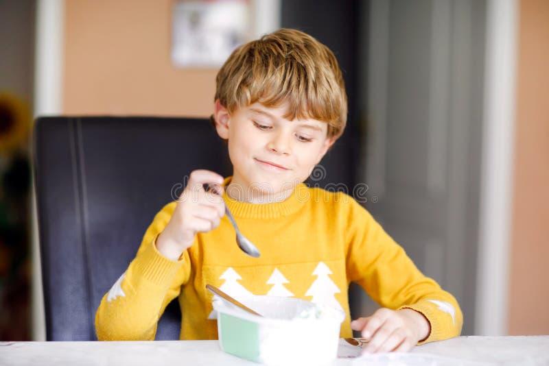 Weinig blonde jong geitjejongen die met krullende haren roomijs eten thuis of in kleuterschool Mooi kind met grote roomijsdoos royalty-vrije stock afbeelding