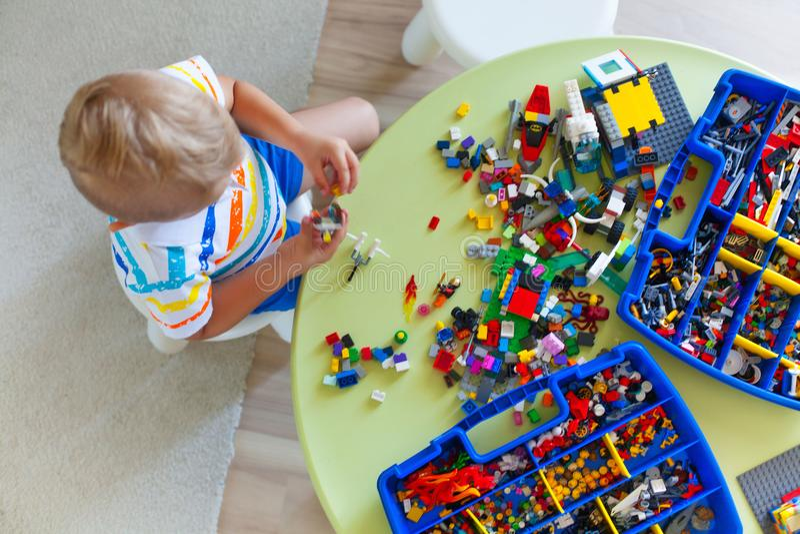Weinig blonde jong geitjejongen die met veel kleurrijk plastic blok spelen stock foto's