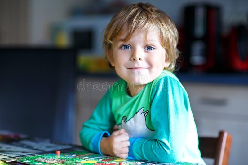 Weinig blonde jong geitjejongen die samen raadsspel thuis spelen Grappig kind die pret hebben stock foto's