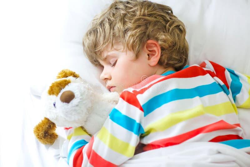 Weinig blonde jong geitjejongen in kleurrijke nachthemden kleedt het slapen stock fotografie