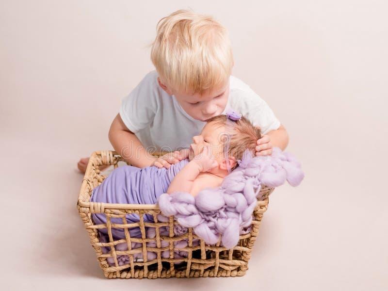 Weinig blonde jongen die weinig baby kussen stock foto