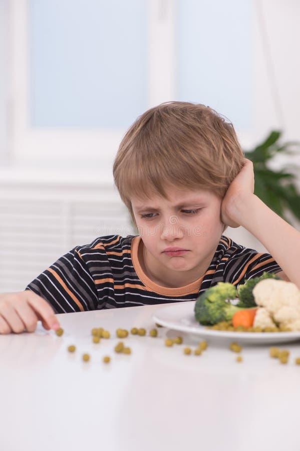 Weinig blonde jongen die bij keuken eten royalty-vrije stock afbeelding