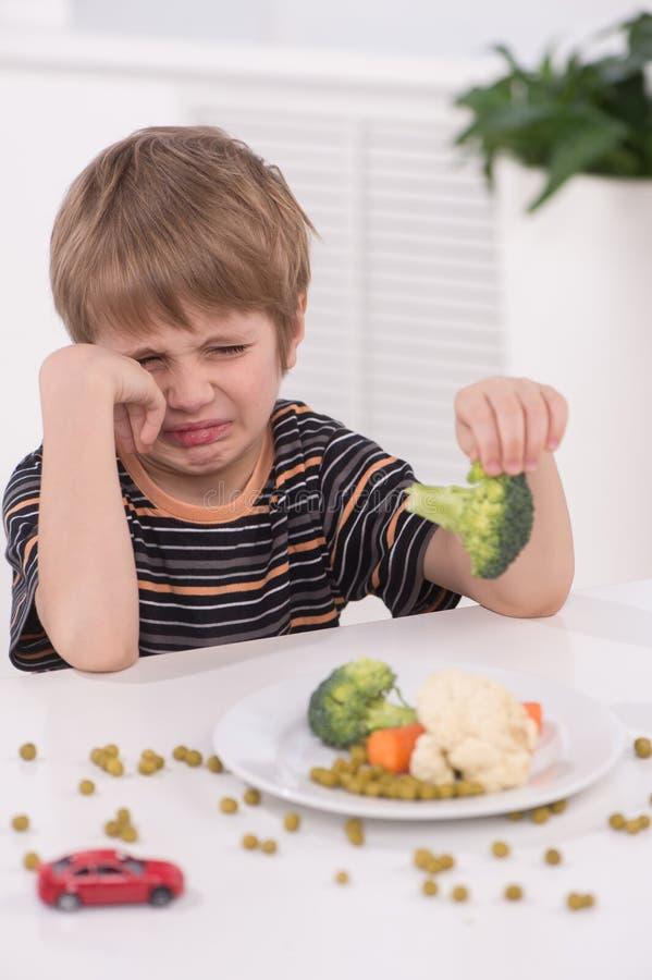 Weinig blonde jongen die bij keuken eten royalty-vrije stock fotografie