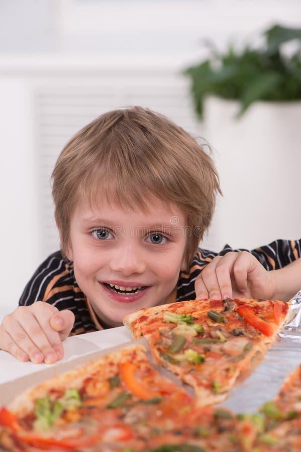 Weinig blonde jongen die bij keuken eten stock afbeelding