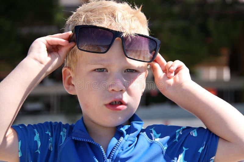 Weinig blonde jongen die grote zonglasees en blauw overhemd dragen stock foto's