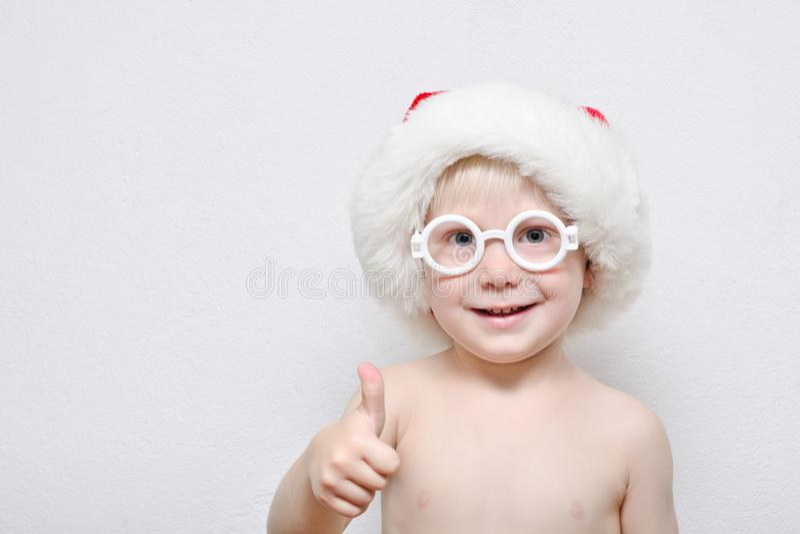 Weinig blonde jongen die Kerstman` s hoed en glazen dragen Duim omhoog stock foto