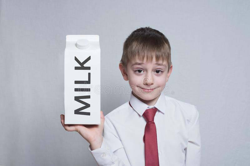 Weinig blonde jongen houdt en toont een groot wit pakket van de kartonmelk wit overhemd en rode band Lichte achtergrond royalty-vrije stock afbeelding