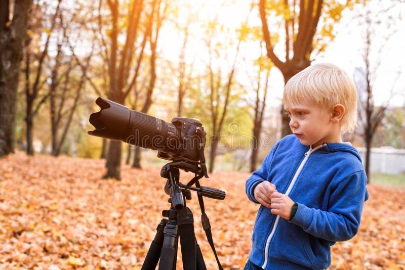 Weinig blonde jongensspruiten met een grote SLR-camera op een driepoot Fotozitting in het de herfstpark royalty-vrije stock afbeelding