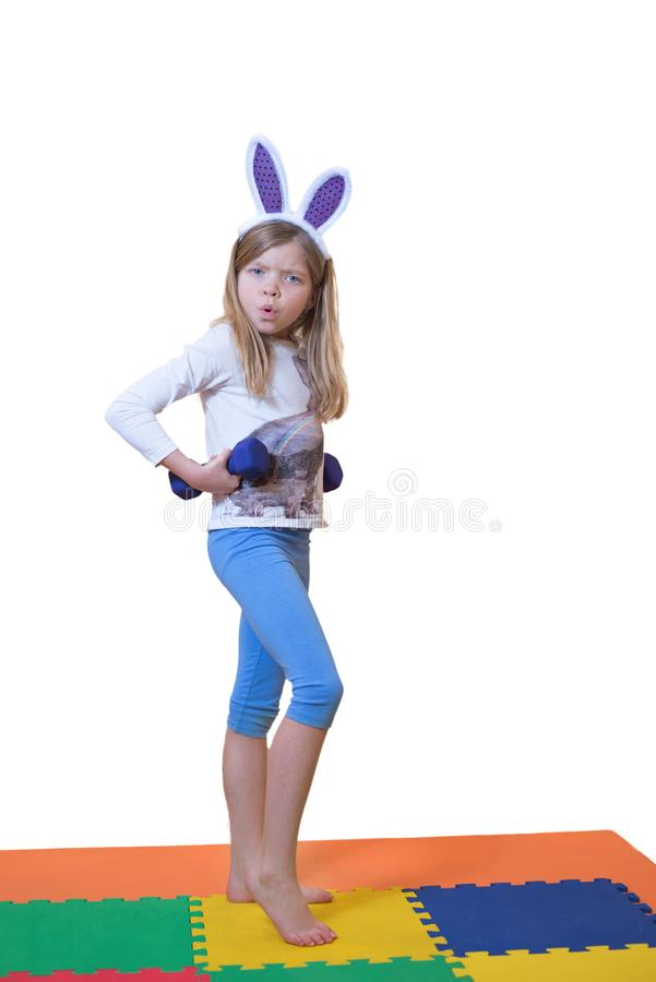 Weinig blonde Kaukasisch meisje doet haar training met domoren Zij draagt in konijntjes` s oren stock afbeeldingen