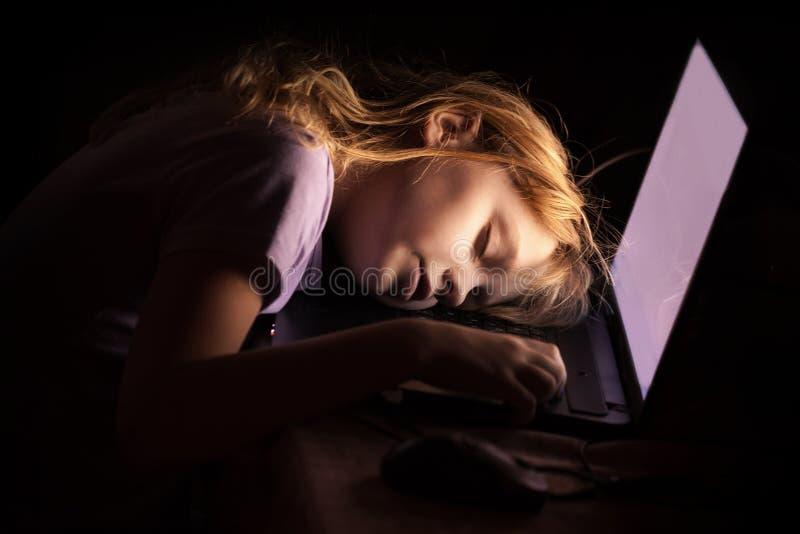 Weinig blonde meisjesslaap op laptop stock afbeelding