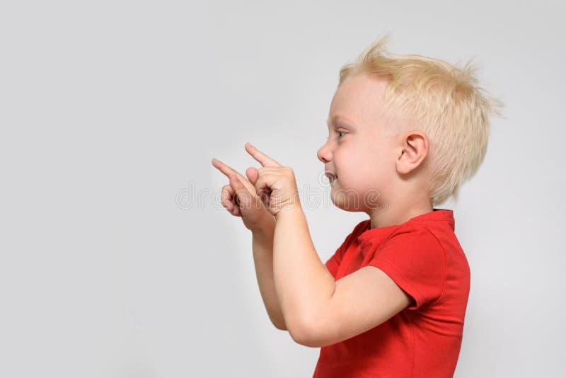 Weinig blondejongen in rode t-shirt richt zijn vinger Ruimte voor tekst Plaats voor Reclame Witte achtergrond royalty-vrije stock foto's
