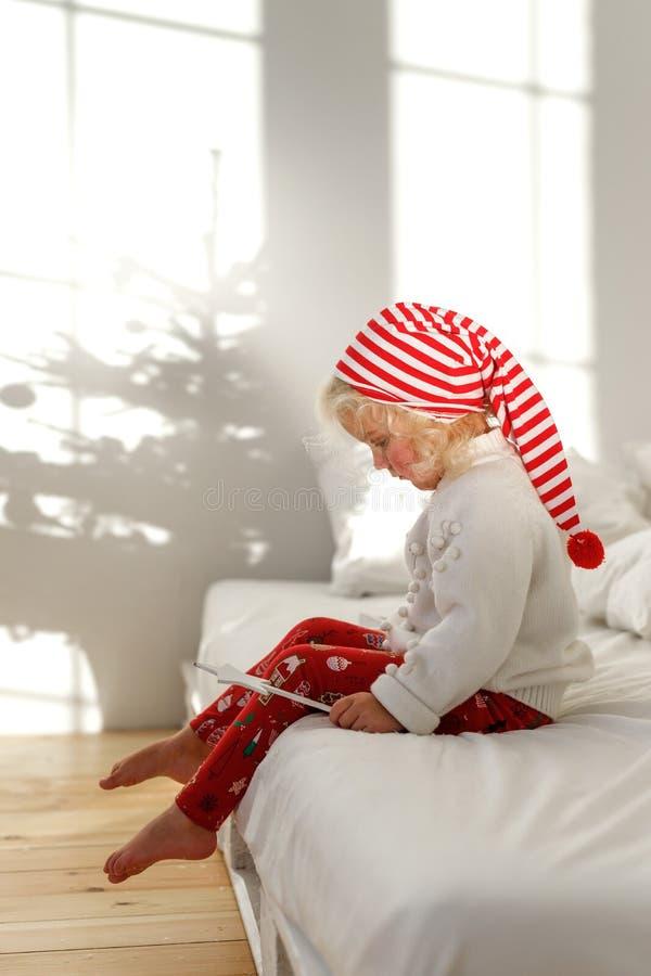 Weinig blondekind in Kerstmishoed zit op bed met wit beddegoed, speelt met toverstokje, heeft geconcentreerd ernstig royalty-vrije stock fotografie