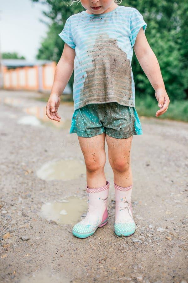 Weinig blondemeisje bekijkt haar vuile kleren na daling in een vulklei stock afbeelding