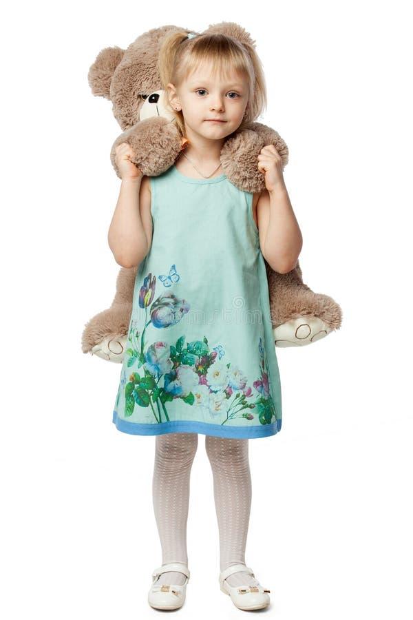 Weinig blondemeisje die een teddybeerstuk speelgoed koesteren royalty-vrije stock foto's