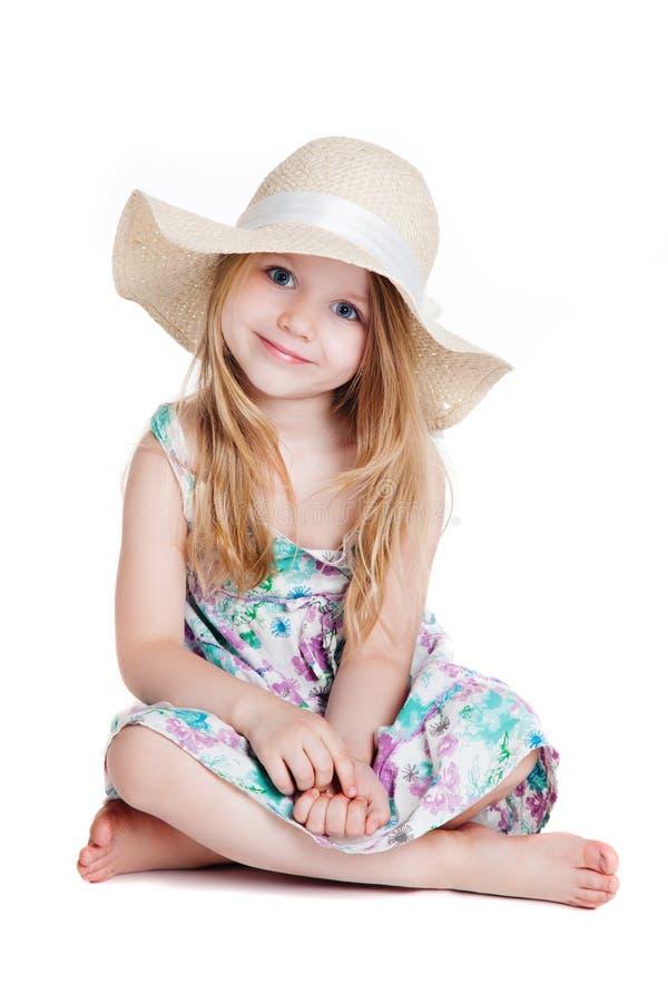 Weinig blondemeisje die hoed en kledingszitting op de vloer dragen stock afbeelding
