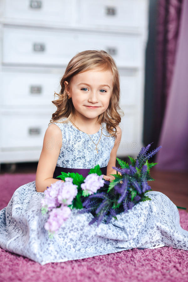 Weinig blondemeisje in een mooie kleding zit op de vloer met bloemen op haar knieën royalty-vrije stock afbeeldingen