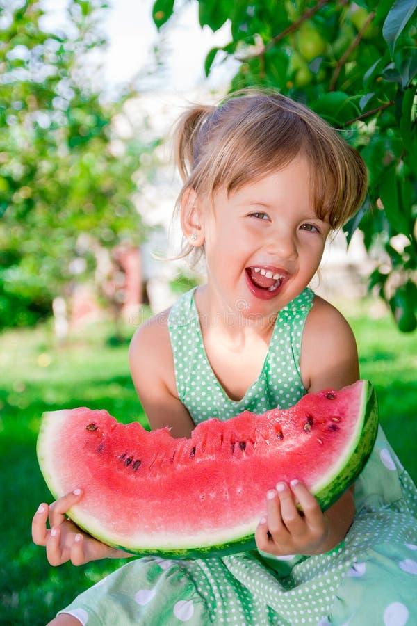 Weinig blondemeisje met grote plakwatermeloen stock fotografie