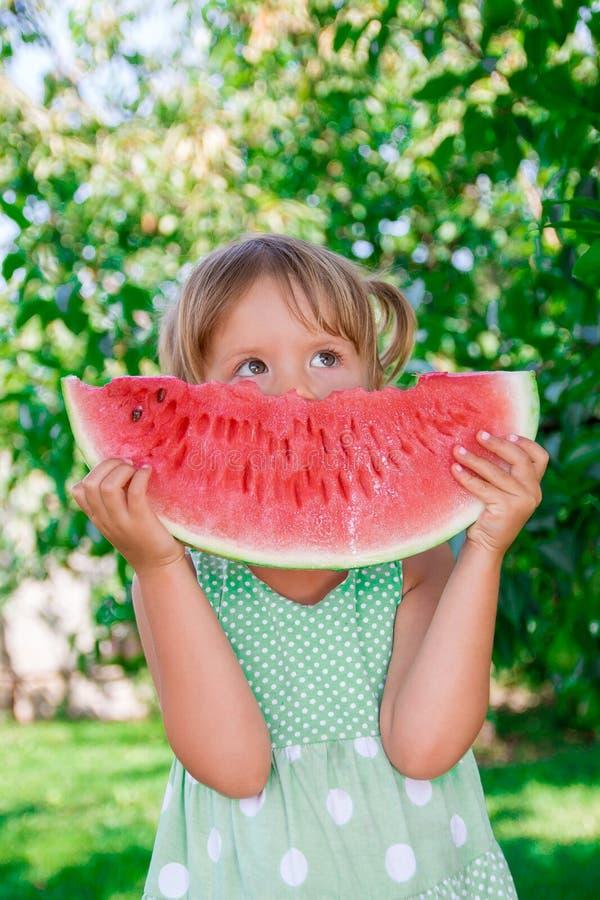 Weinig blondemeisje met grote plakwatermeloen stock afbeeldingen