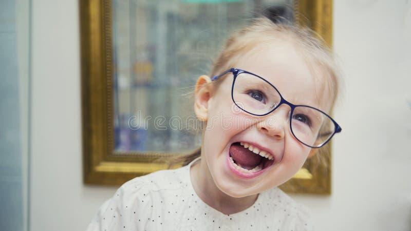 Weinig blondemeisje in zaal van oftalmologiekliniek heeft pret en spelen met glazen royalty-vrije stock afbeeldingen