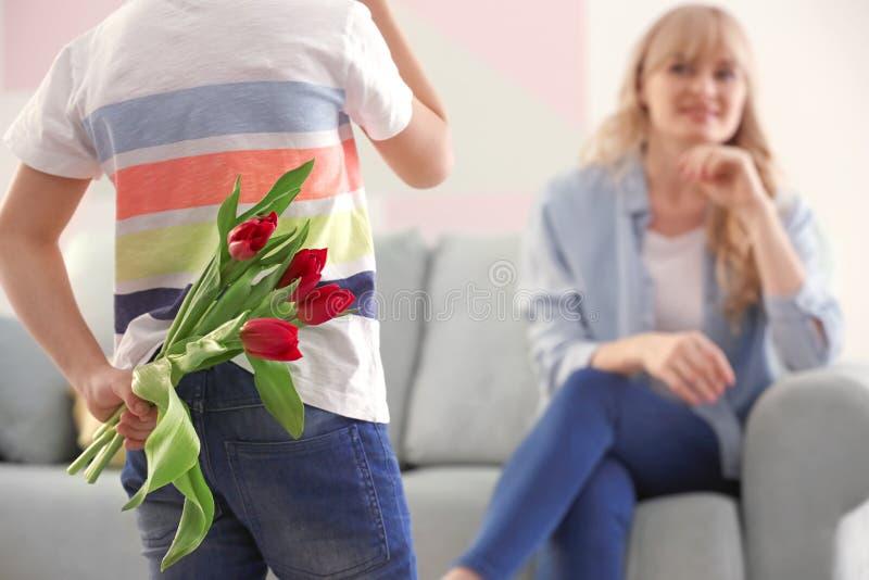 Weinig boeket van de jongens verbergend tulp voor moeder achter zijn rug thuis royalty-vrije stock fotografie