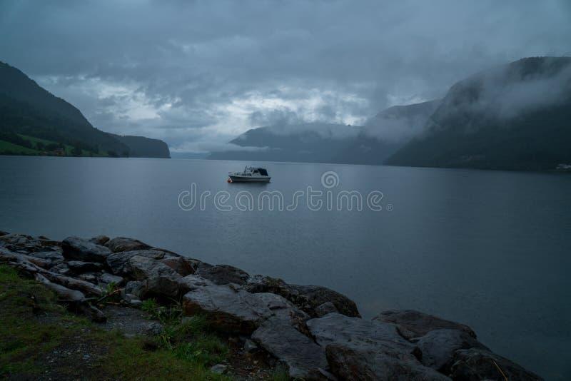 Weinig boot op een meer een geheimzinnigheid bewolkte dag in de fjord van Noorwegen geiranger royalty-vrije stock fotografie