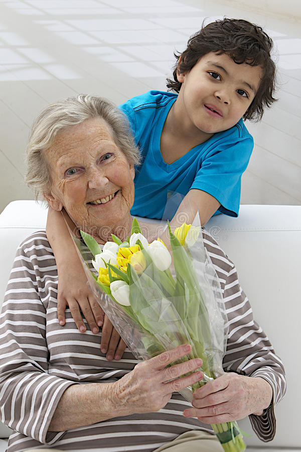 Weinig boying aanbiedende bloem aan zijn grootmoeder stock afbeelding