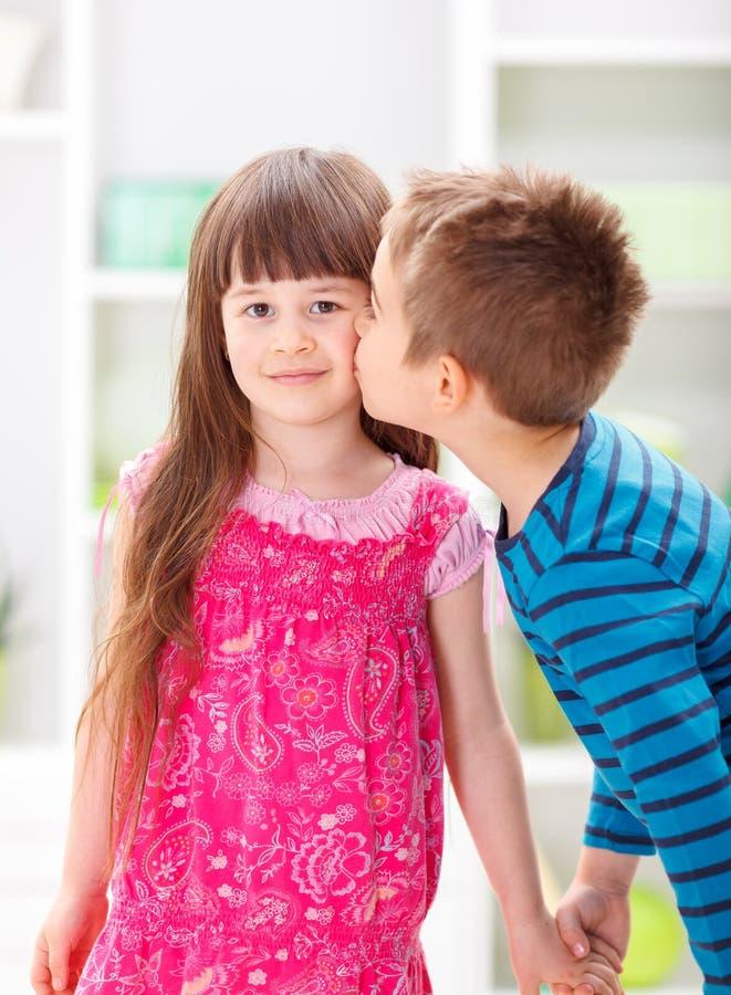 Weinig broer die zijn zuster kussen stock foto