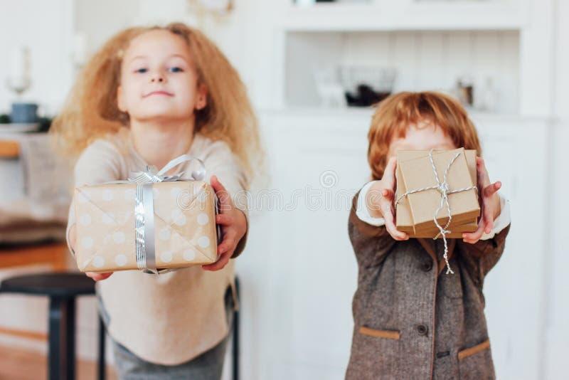 Weinig broer en zuster geven giften Nadruk op dozen, gestemde foto stock afbeeldingen