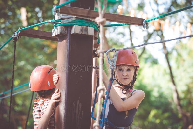 Weinig broer en zuster maken het beklimmen in het avonturenpark royalty-vrije stock afbeelding
