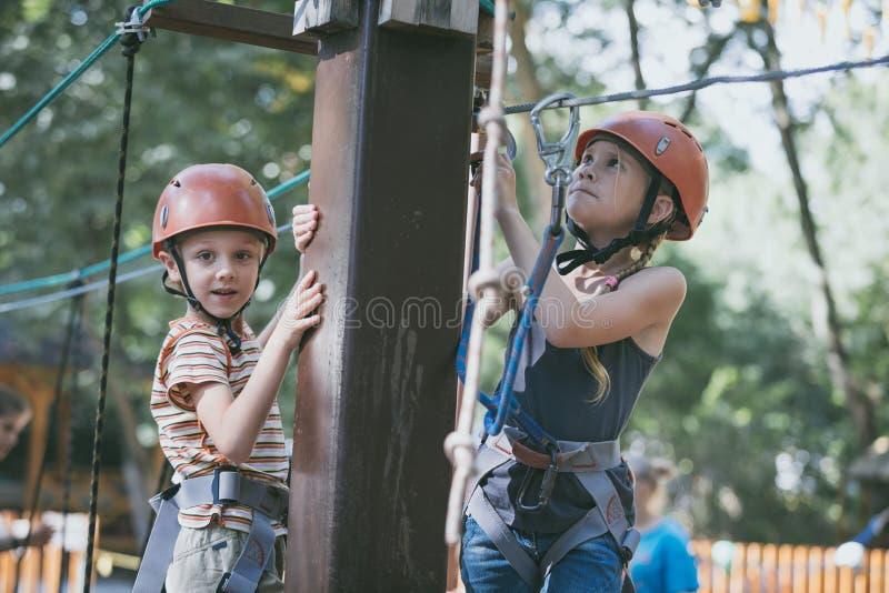 Weinig broer en zuster maken het beklimmen in het avonturenpark royalty-vrije stock foto