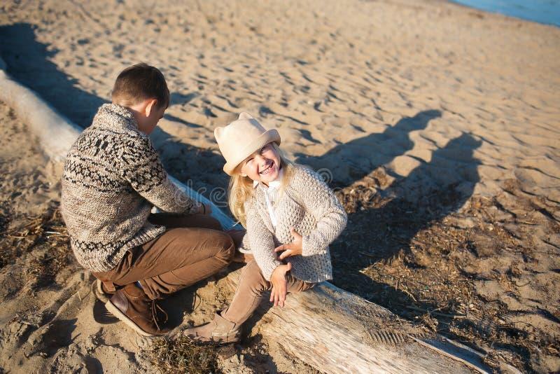 Weinig broer en zuster zitten op een oude straal op een strand royalty-vrije stock afbeelding